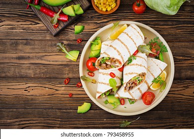 Burritos wraps with beef and vegetables on a wooden background. Beef burrito , mexican food. Healthy food background. Mexican cuisine.Top view.