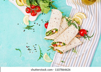 Burritos wraps with chicken and vegetables on light  background. Chicken burrito, mexican food. Top view, flat lay