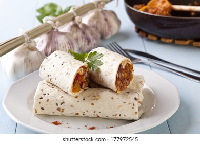 burritos wraps with meat beans and vegetables on blue wood board