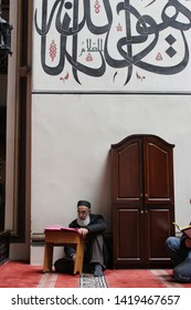 Bursa, Turkey - April 5,  2014: Old bearded man reading holy Quran and praying in the mosque. Arabic caligraphy on the wall in Grand Mosque, Ulucami.