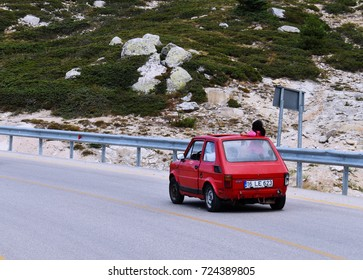 BURSA, TURKEY - AUGUST 29, 2017 : Girl wearing pink-colored t-shirt looks around from sunroof of small red car driven on asphalt road in mountain area in Turkey's Uludag, Bursa