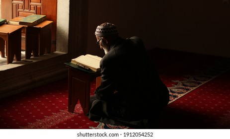 Bursa, Turkey - March 2020: Unidentified muslim old religious man reads Quran concept. Reading Quran is kind of a worship in Islam. Middle eastern older man praying and reading the holy Quran.
