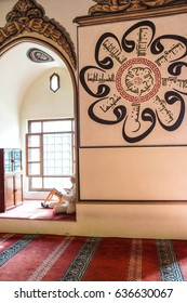 BURSA, TURKEY - MAY 22, 2014 - Man sits in an alcove of the mosque before afternoon prayers, with Islamic calligraphy on the wall behind him,  in the Ulu Cami Bursa, Turkey