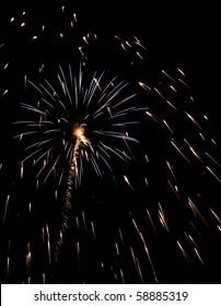 Burst of bluish fireworks inside cloud of falling embers