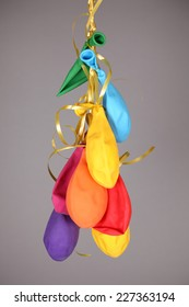 Burst, deflated balloons tied with gold twisted ribbons on grey background