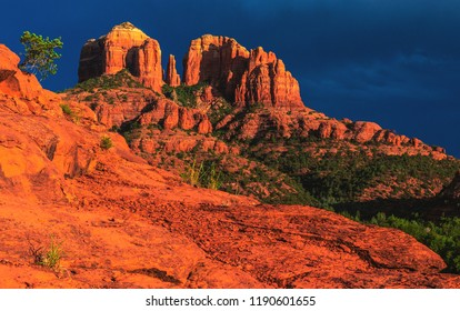 A burst of sun after a thunderstorm spills light onto Cathedral Rock and the surrounding sandstone in Sedona, Arizona, USA.