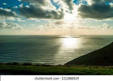 A burst of sunlight through dark clouds onto ripples of waves