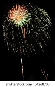 Burst of yellow-orange fireworks inside cloud of falling embers