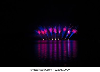 Bursts of blue and violet fire in rich fireworks over Brno's Dam with lake reflection