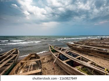 Burundi Bujumbura lake Tanganyika, windy cloudy sky and sand beach at sea lake in East Africa, Burundi sunset with boats from wood. Storm weather