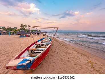 Burundi Bujumbura lake Tanganyika, windy cloudy sky and sand beach at sea lake in East Africa, Burundi sunset with boat from wood. Thatch african roofs on umbrellas