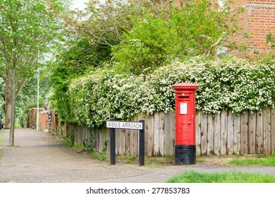 BURY ST EDMUNDS, ENGLAND - 11 MAY 2015: Vintage British postal pillar box with gold crown and GR cypher cast into front  at Avenue approach road, Bury St Edmunds, UK.