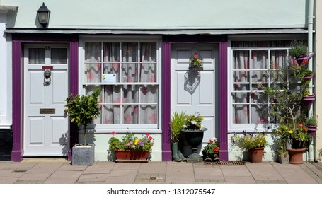 BURY ST EDMUNDS, SUFFOLK, UK - AUGUST 4, 2018. A terraced house with its pavement potted garden, once two tiny 18th century shops at Bury St Edmunds, Suffolk, England, UK.