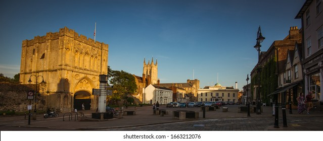 Bury St Edmunds, Suffolk / United Kingdom - June 1 2017: A view across Angel Hill in Bury St Edmunds showing the Abbey Gate and Cathedral Tower in orange evening sun, as well as the Athenaeum