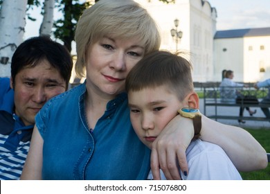 Buryat family.  Mother with son and father behind.