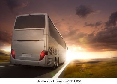 Bus driving on a road in the sunset