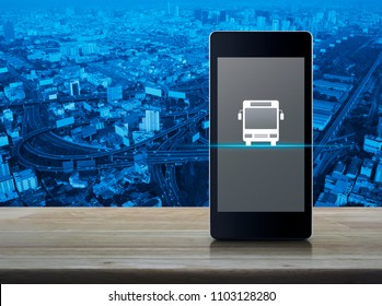 Bus flat icon on modern smart phone screen on wooden table over city tower, street and expressway, Business transportation service concept