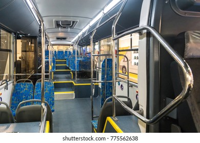 Bus interior inside. Blue seats and metal handrails