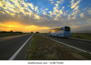 Bus moving on high-speed highway at sunset.