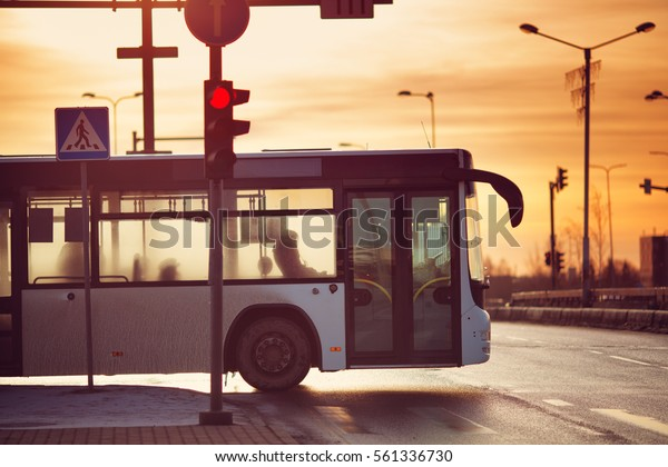 Bus moving on the road in city in early morning. View to the traffic with trafficlights and transport