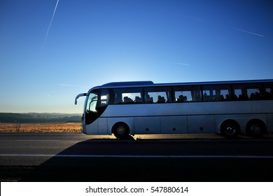 Bus on the road at sunset