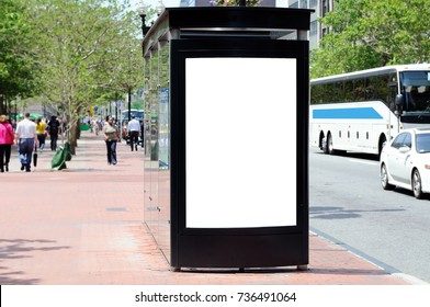 Bus shelter advertising. Blank billboard on brick sidewalk, people and traffic on the background