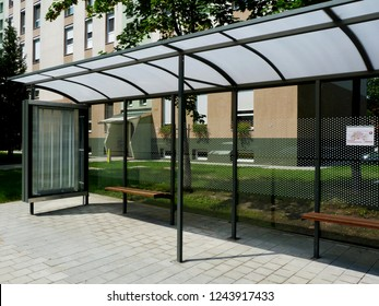 bus shelter at a bus stop of glass and aluminum structure in park-like setting in day time with green background and appealing polka dot safety glass design and wooden benches & poster display glass