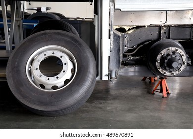 bus spare wheel tire waiting to change and axle bus on the lifting jack at the garage