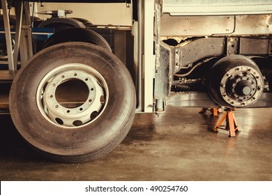 bus spare wheel tire waiting to change and axle bus on the lifting jack at the garage, vintage photo and film style