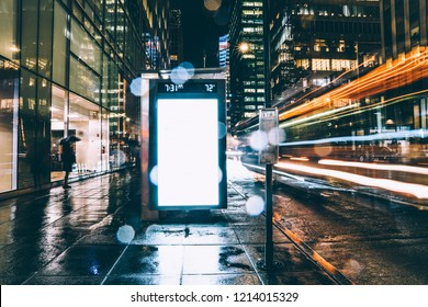 Bus station billboard in rainy night with blank copy space screen for advertising or promotional content, empty mock up Lightbox for information, clear display in urban city street with long exposure