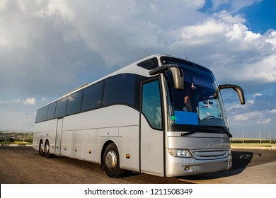 Bus staying in the parking lot under a blue sky with clouds. Lateral view of a bus