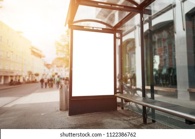 Bus stop billboard mockup. Sun light and street in background.