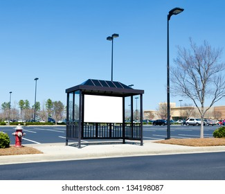 Bus stop with billboard near large shopping center area parking