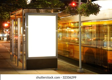 Bus stop billboard at night. Bus passing by
