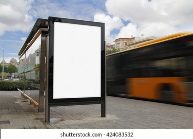 Bus stop with blank billboard, with blurred motion bus
