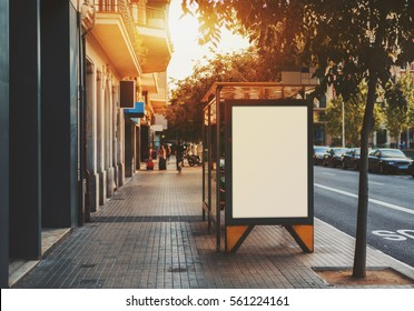 Bus stop in city with empty white mock up banner for advertising, clear public information board in urban setting in sunny summer day, blank billboard with copy space section for informational message