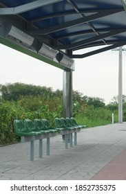 A bus stop green chair on foot sidewalk.