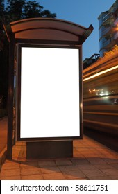 Bus stop at night. Blurred light from the passing vehicles are visible. This is for advertisers to place ad copy samples on a bus shelter.