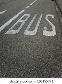 Bus stop sign painted on public asphalt road.