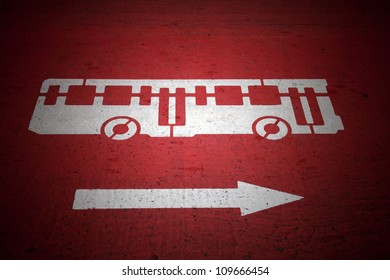 Bus and traffic direction sign painted on red asphalt road