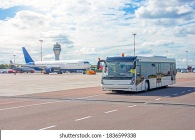 Bus for transporting passengers to boarding aircraft, against the background of a taxiing airliner on the apron of the airfield with a control atc tower