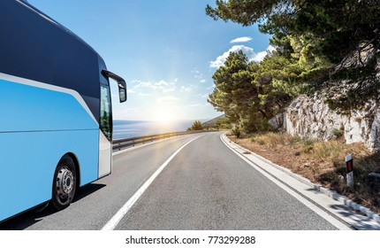 Bus Travel. The tourist bus rushes along the country high-speed highway against the background of a mountain landscape cliff next to the sea.