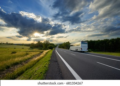 Bus traveling on the asphalt road in a rural landscape at sunset with dramatic clouds