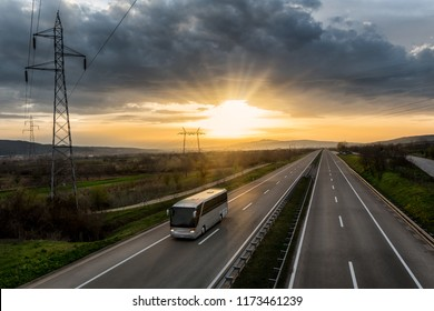 Bus traveling on a lonely countryside Highway with the sunset behind