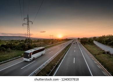 Bus traveling on a lonely countryside Highway with beautiful sunset behind