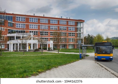 Bus waiting at a bus stop in front of public school building made of red bricks