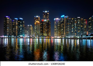 Busan Marina city skyscrapers illluminated in night with reflection in water, South Korea