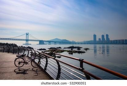 Busan Seascape. Bike standing on the boardwalk by the Beach and nearby Gwangan Bridge in Busan City, Korea.