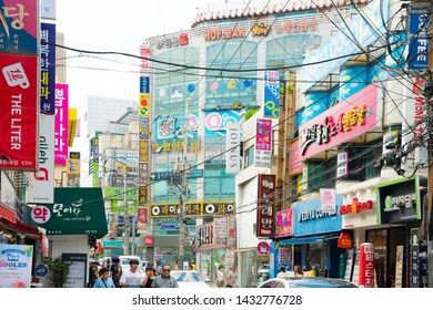 Busan, South Korea - 11Aug 2018: Jung-dong street scene daytime featuring the dense and colorful signs of boutiques and restaurants. Several people are seen on the sidewalk or crossing the street,