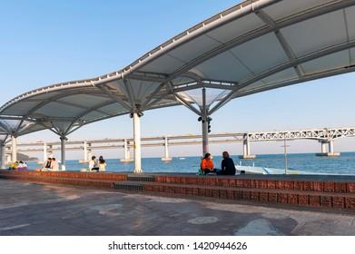 Busan, South Korea - April 2019: People relaxing and enjoying view of Busan Gwangandaegyo Bridge or Diamond Bridge at Millak Waterside Park in Busan, South Korea